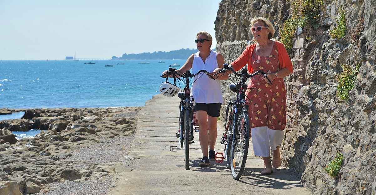 Women pushing bikes by the sea on the Isle of Wight